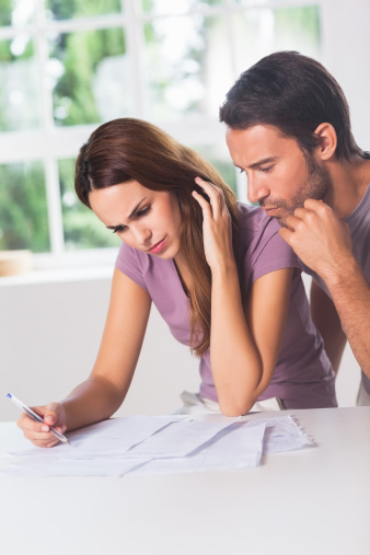 Couple figuring out what to do about a reduction in their income.