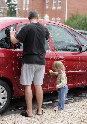 A little girl helping her Daddy wash Mom's car for Mother's Day