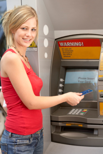 Young woman withdrawing cash from an ATM.